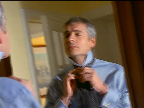 PAN man looking in wardrobe mirror putting on necktie