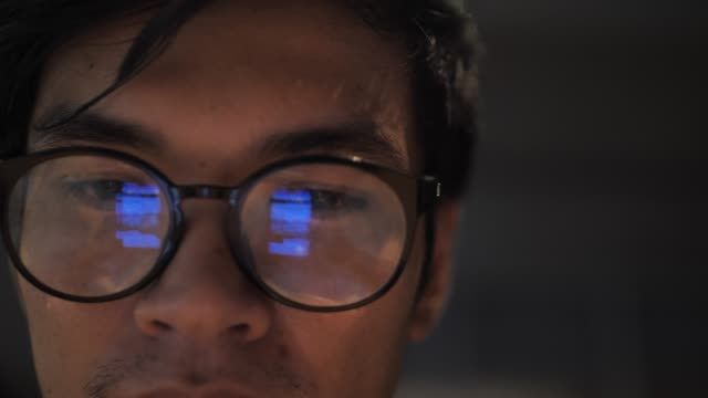 Man looking on Smart phone and Reflection on Eyeglasses
