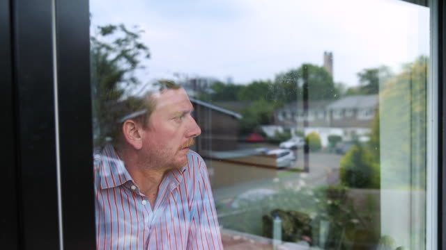 man looking out of window. the reflection shows suburbia - one person stock videos & royalty-free footage