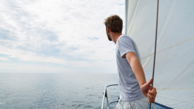 ms man looking out over mediterranean sea on classic wooden sailing yacht - maglietta video stock e b–roll