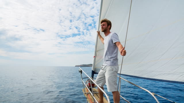 MS man looking out over mediterranean sea on classic wooden sailing yacht