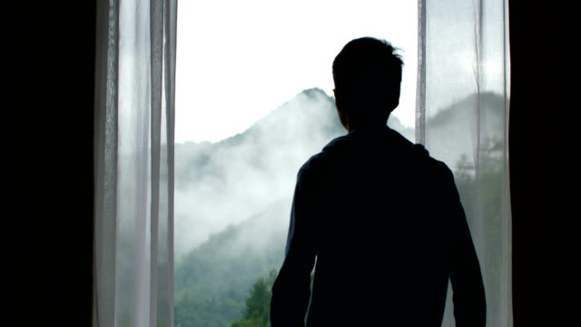 man looking out over mountain in doors - looking through window stock videos & royalty-free footage