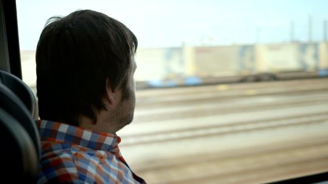 vidéos et rushes de hd : homme regardant par la fenêtre en train - transports publics