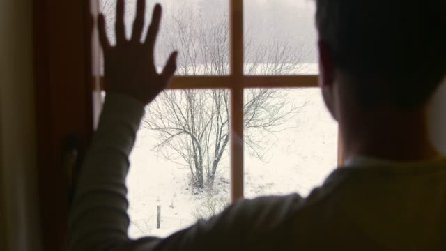 man looking out window at view of snowy winter yard, super slow motion - looking through window stock videos & royalty-free footage