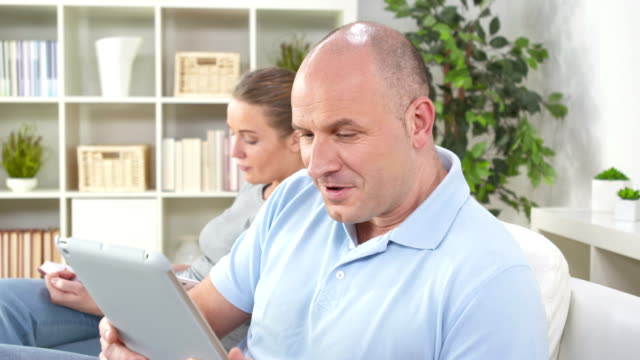 hd dolly: mann, die etwas schockierend auf ein tablet - schockiert stock-videos und b-roll-filmmaterial