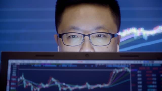 vídeos de stock, filmes e b-roll de homem olhando mercado de ações dados no computador - casa de câmbio