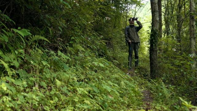 Man looking through binoculars in foreast
