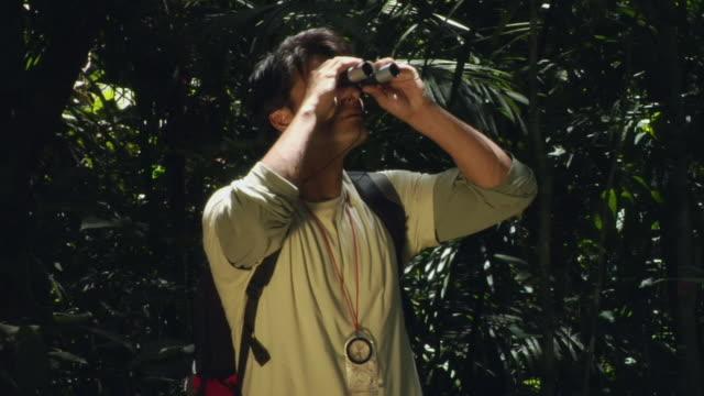 MS, Man looking through binoculars in forest, Manaus, Brazil