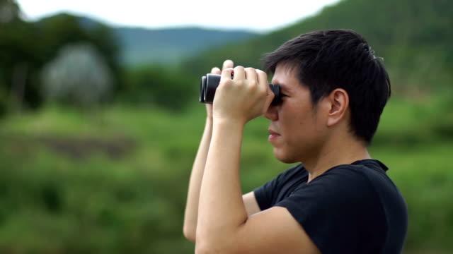 blick durch ein fernglas in natur gebirgshintergrund mann - menschliches auge stock-videos und b-roll-filmmaterial