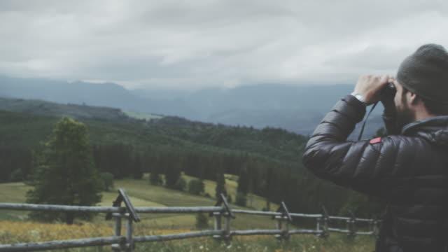 mann sucht durch ein fernglas. bergige landschaft - fernglas stock-videos und b-roll-filmmaterial