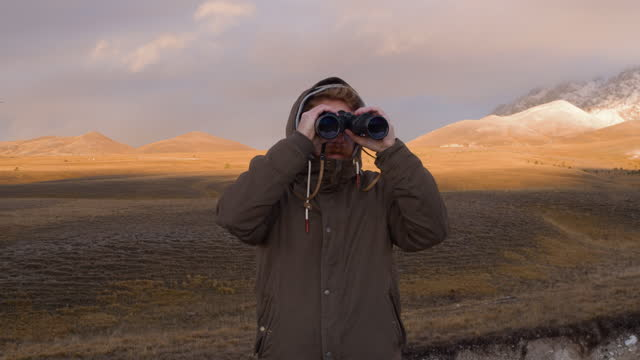man looking through binoculars with the mountains in the background. - binoculars stock videos & royalty-free footage