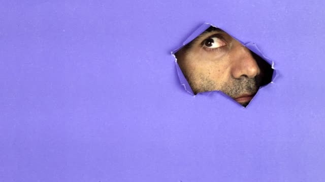 man looking through colorful torn paper - privacy stock videos & royalty-free footage