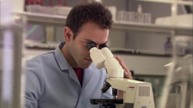 cu, man looking through microscope in laboratory, london, england - centro di ricerca video stock e b–roll
