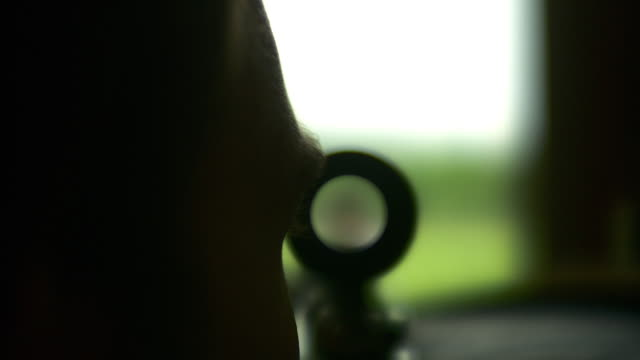 cu r/f man looking through rifle scope and seeing another man pointing handgun, stowe, vermont, usa - ライフル点の映像素材/bロール