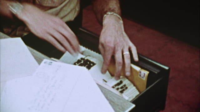 vídeos de stock, filmes e b-roll de cu, pan, man looking through rolodex and using phone, close up of hands, 1970's, los angeles, california, usa - 1973