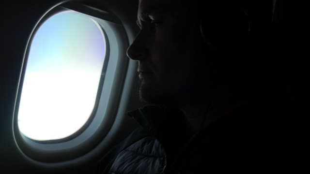 A man looking through the airplane window