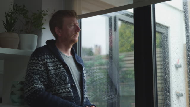 man looking through window - cardigan sweater stock videos & royalty-free footage