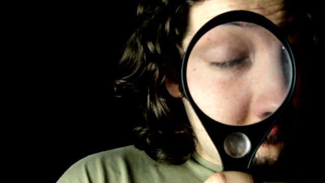 man looking throught magnifying glass - eyesight stock videos & royalty-free footage