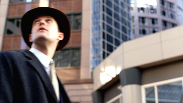 vídeos de stock e filmes b-roll de man looking up at sky, then walking towards building - fato completo