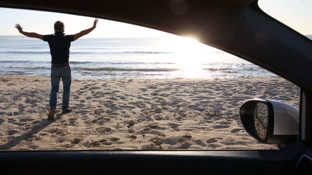 stockvideo's en b-roll-footage met man looks across empty beach from parked car, walks onto beach - uitstappen