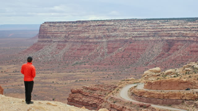 A man looks across the Moki Dugway