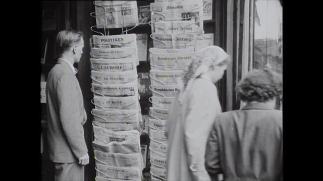 a man looks at international newspapers in different languages at a newspaper stall in helsinki during the 1952 summer olympics - 1952 stock videos & royalty-free footage
