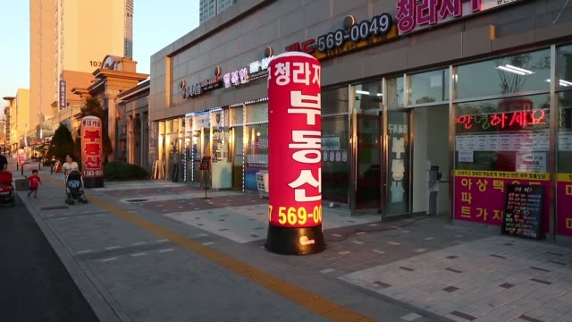 stockvideo's en b-roll-footage met a man looks at property advertisements displayed outside a real estate agency at cheongna international city in incheon south korea on sunday sept 1... - incheon