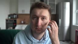 A man looks at the camera at home, inserts a wireless headset into his ears