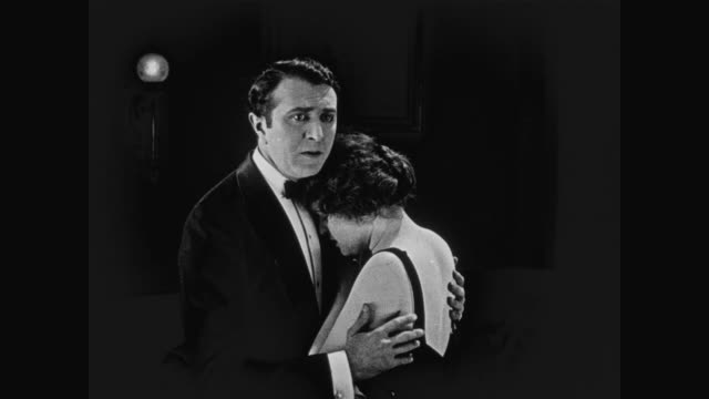 1920 a man looks distraught as he embraces a woman - 無声映画点の映像素材/bロール