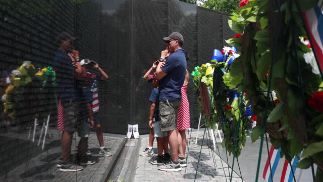 A man looks for a name at the Vietnam Wall on Memorial Day