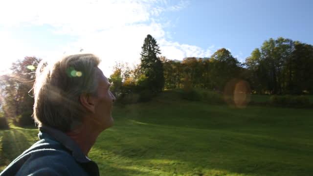 Man looks off across autumn meadow, sunrise