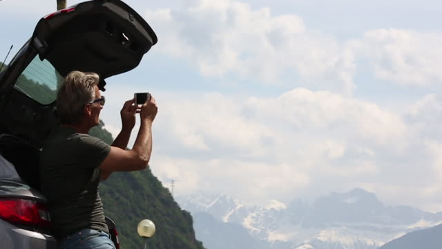 mann sieht aus nach mountain view, straßenrand pic entnimmt - heckklappe teil eines fahrzeugs stock-videos und b-roll-filmmaterial