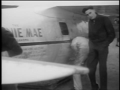 vidéos et rushes de b/w 1935 man looks on as men clean winnie mae prop plane on airfield / cleveland oh / newsreel - 1935