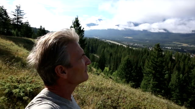 Man looks out across mountains from grassy ridge