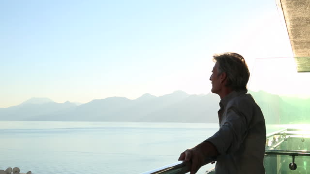 man looks out across sea from hi-rise deck, contemplatively - endast en medelålders man bildbanksvideor och videomaterial från bakom kulisserna
