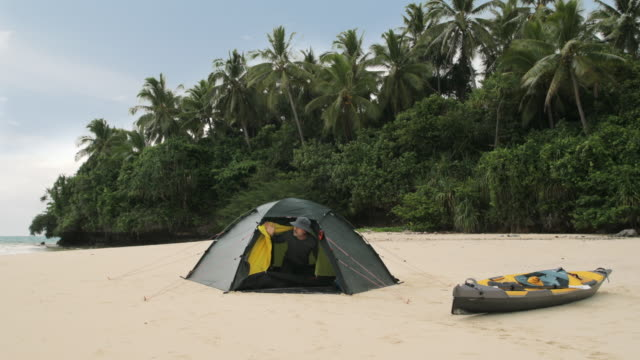MS A man looks out of a tent on a Pacific island