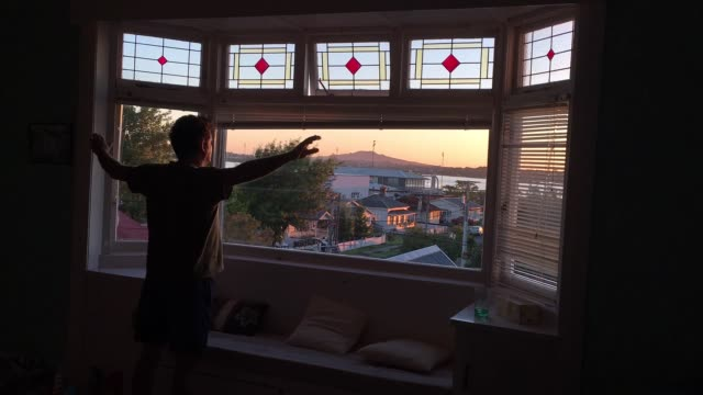 Man looks out of his home window during sunrise morning