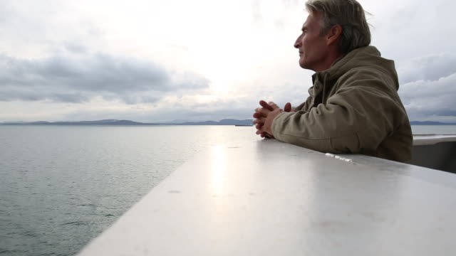 vidéos et rushes de man looks out to sea from bow of moving ferry - ferry