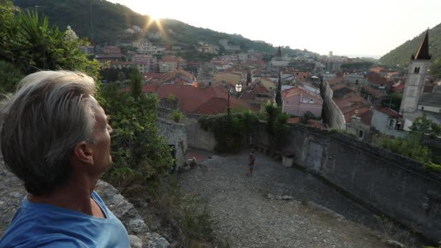 man looks over cobblestone path and village at sunrise - cultura italiana video stock e b–roll