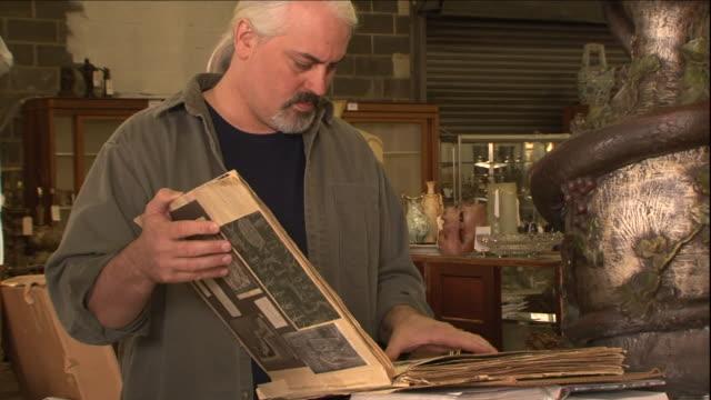 vídeos de stock, filmes e b-roll de a man looks through antique documents. - antiquário loja