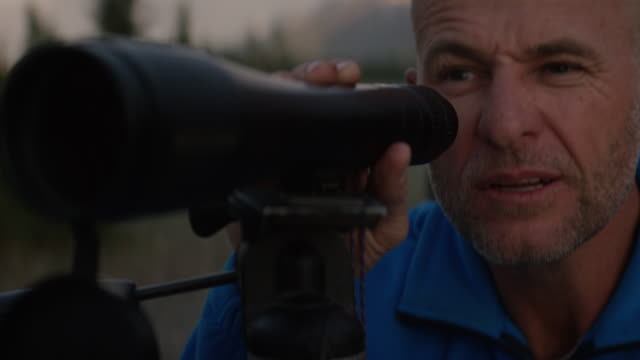 man looks through telescope on the banks of a beautiful river in he mountains - balding stock videos & royalty-free footage