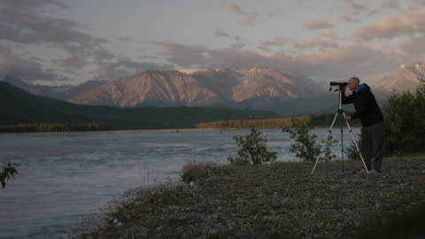 man looks through telescope on the banks of a beautiful river in he mountains - biologist stock videos & royalty-free footage