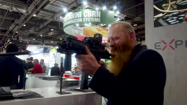 man looks through the site of gun on the beretta display stand. - showing stock videos & royalty-free footage
