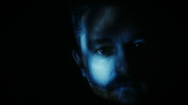 man looks to camera under blue light - staring stock videos & royalty-free footage