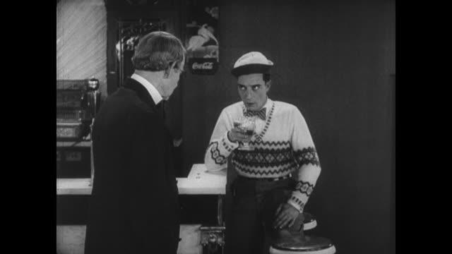 stockvideo's en b-roll-footage met 1927 man (buster keaton) loses his job when he gets caught posing as a customer - ontslaan