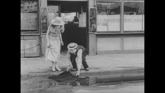 vidéos et rushes de 1923 man (buster keaton) loses woman after laying down coat over puddle for her - règle de savoir vivre