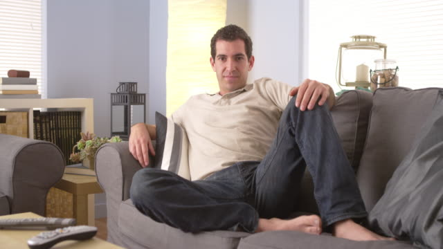 stockvideo's en b-roll-footage met man lounging on sofa - achterover leunen