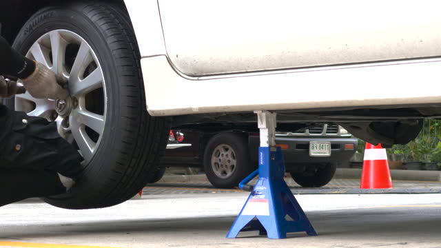 man lowers a car body with a jack - service stock videos & royalty-free footage