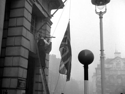 vídeos de stock e filmes b-roll de a man lowers a union jack flag to half mast on the exterior of a building after the announcement of the death of queen mary 1953 - baixar
