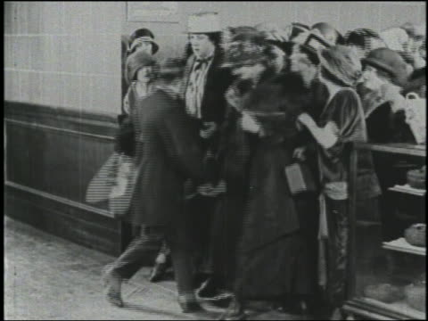 b/w 1924 man lowers rope, crowd of women rush into store for sale / man is run over - chaos stock-videos und b-roll-filmmaterial